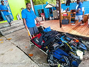 dive dominica dive staff taking dive gear to the boat